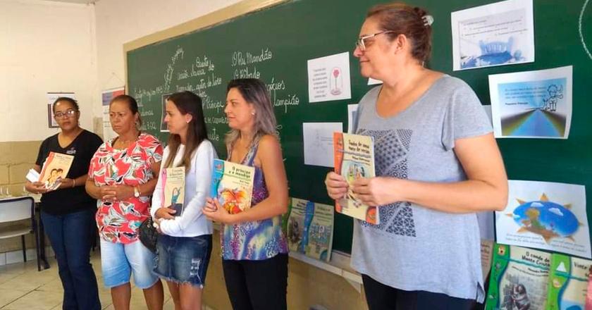 Em sala de aula, cinco mulheres apresentam livros à turma. Fim da descrição.
