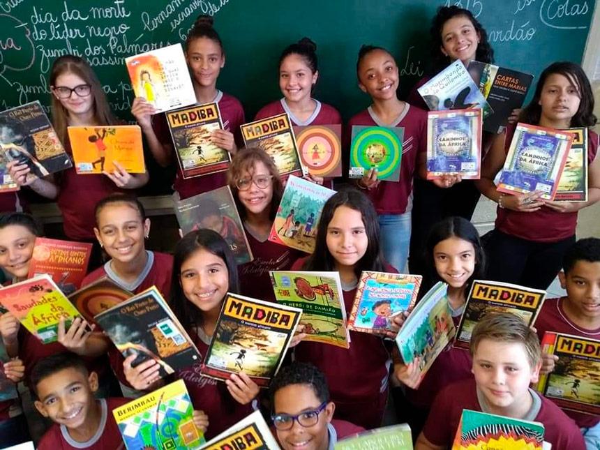 Em sala de aula, estudantes uniformizados sorriem para foto. Cada um segura dois livros nas mãos, mostrando suas capas; a maioria dos livros é sobre cultura africana. Fim da descrição.