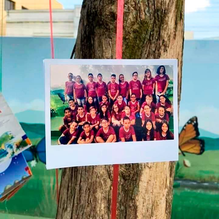 Foto impressa de estudantes uniformizados está pendurada em árvore com fita vermelha. Fim da descrição.