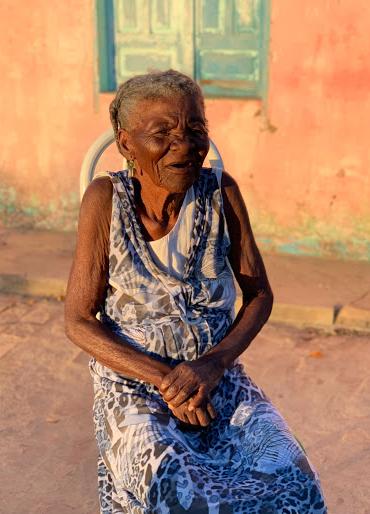 Idosa está sentada em cadeira na rua e posa para foto. Ao fundo, casa com pintura rosa e janela azul. Fim da descrição.