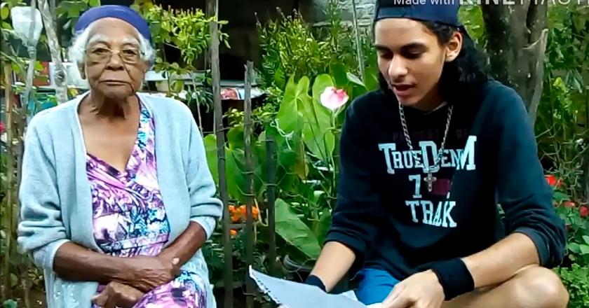 Jovem e sua avó sentados lado a lado. O estudante lê algo de papel em sua mão. A idosa olha para a câmera. Fim da descrição.