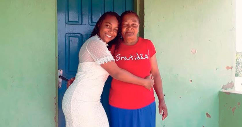 Estudante abraçada com avó. Ambas sorriem para a foto. Ao fundo, parede verde claro e porta azul. Fim da descrição.