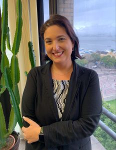 Em escritório, Debora Salles sorri para foto em frente à janela e ao lado de um cacto doméstico. Fim da descrição.