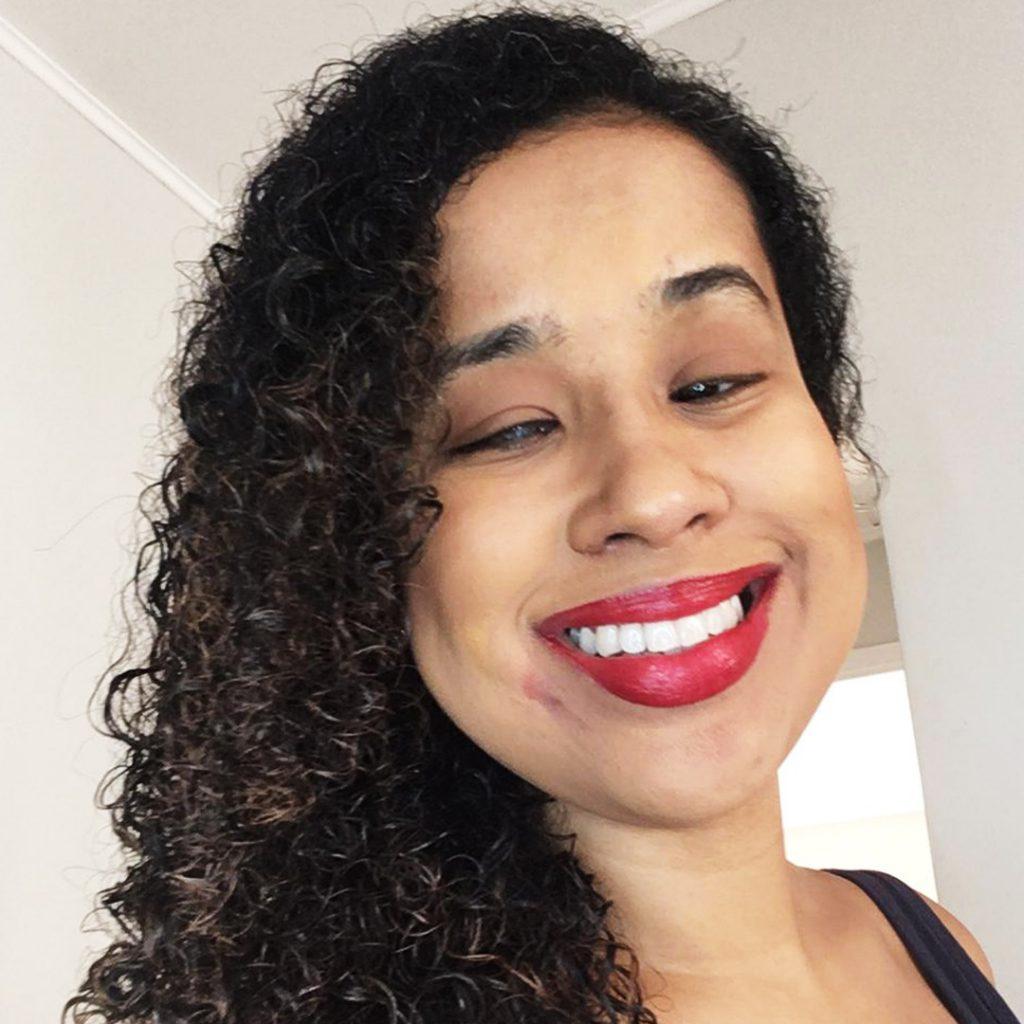 Lara Souto sorri . Ela é uma mulher negra na faixa dos 20 anos e com cabelos pretos cacheados.  Usa batom vermelho. Ao fundo, uma parede branca. Fim da descrição.