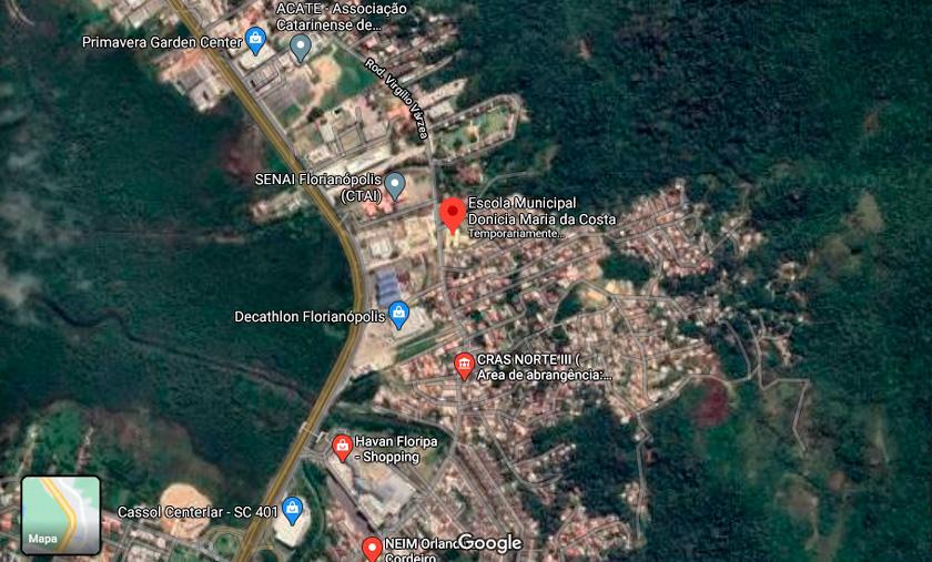 Imagem aérea do entorno escolar com quarteirões e quadras próximas à escola. Há grandes áreas verdes ao redor. Fim da descrição.