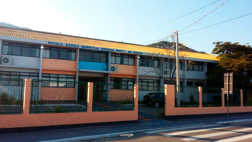 Fachada da Escola Municipal Donícia Maria da Costa, em Santa Catarina. A unidade possui muros nas cores laranja e branco e portões verdes. Na rua à frente, há uma faixa de pedestres. Fim da descrição.