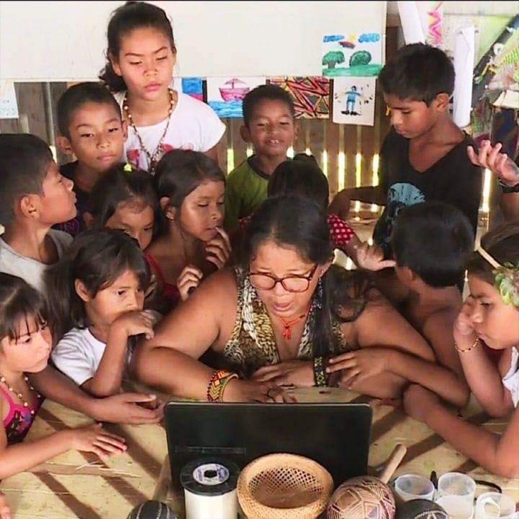 Sentada em cadeira e em frente a notebook, Claudia Baré é rodeada por pequenos estudantes indígenas. Ela usa óculos e pulseiras nos braços. Fim da descrição.