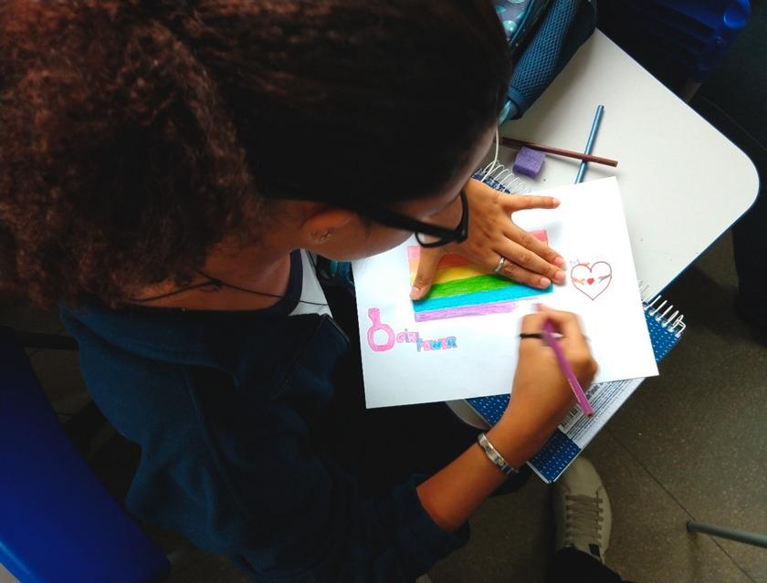 """Estudante realiza desenho com as cores da bandeira lgbt e com os dizeres """"girl power"""". Fim da descrição."""
