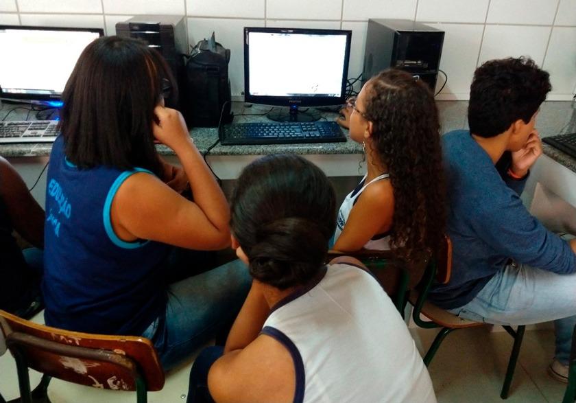Em laboratório de informática, três alunas uniformizadas olham para tela de computador. Fim da descrição.