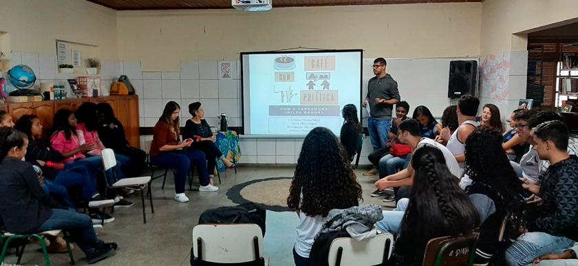 Em auditório, professor Diogo em pé discursa para estudantes ao lado de apresentação projetada. Estudantes o observam sentados em cadeiras. Fim da descrição.