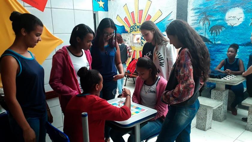 Em pátio escolar, estudantes se reúnem ao redor de mesa em que duas alunas jogam jogo de tabuleiro. Ao fundo há desenhos coloridos. Fim da descrição.