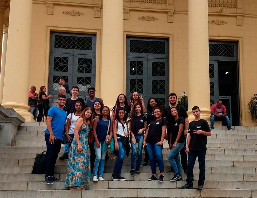 Em frente a câmera de vereadores, grupo de 12 estudantes posa para foto em pé. Fim da descrição.