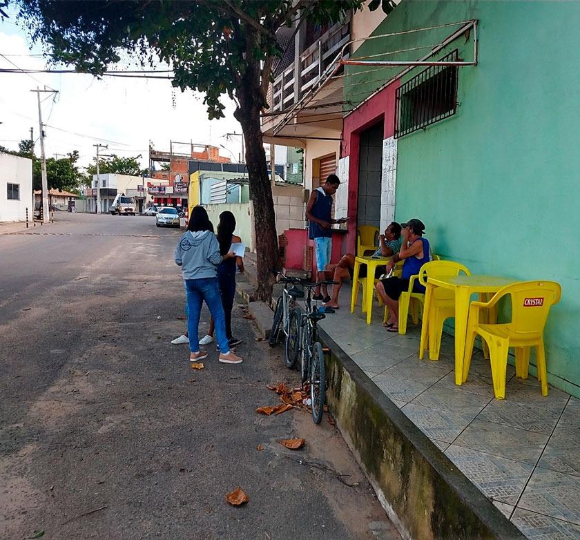 Em entrada de bar, três estudantes abordam para pesquisa duas senhoras sentadas em mesa amarela. Fim da descrição.
