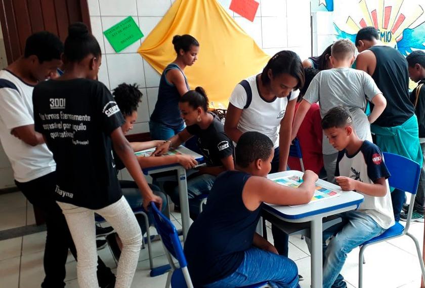 Em pátio escolar, estudantes se reúnem ao redor de mesas em que colegas jogam jogo de tabuleiro. Fim da descrição.