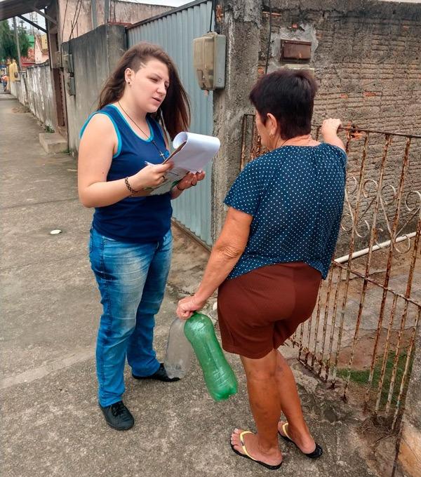 Em rua de bairro, estudante realiza questionário com moradora do bairro. A aluna segura um caderno em suas mãos, enquanto a entrevistada apoia braço direito em grade de portão e segura garrafa Pet com a mão esquerda. Fim da descrição.