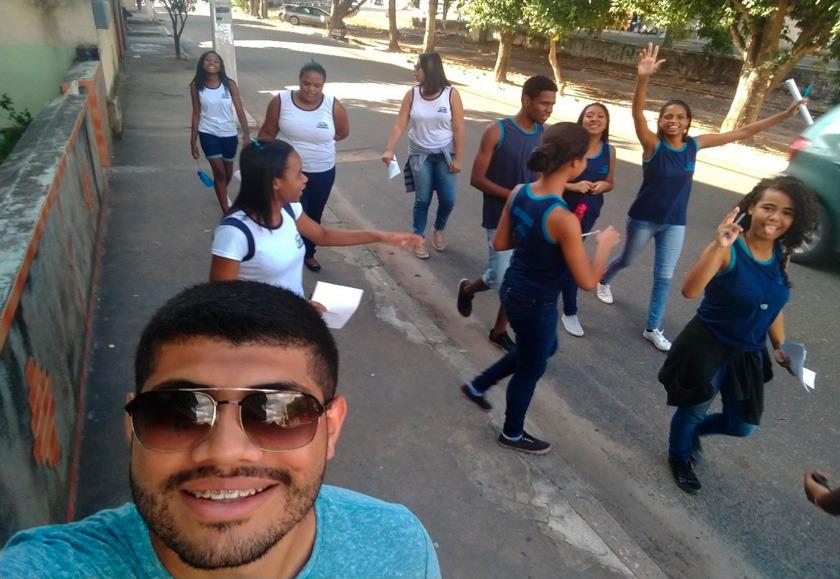 Em calçada de rua, professor Diogo tira selfie sorridente. Ao fundo, grupo de estudantes uniformizadas andam por calçada, enquanto alguns alunos passeiam pela rua. Fim da descrição.