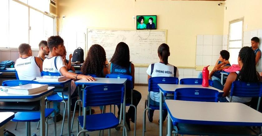 Em sala de aula, estudantes sentados em carteiras acompanham documentário reproduzido em TV acima da lousa. Fim da descrição.