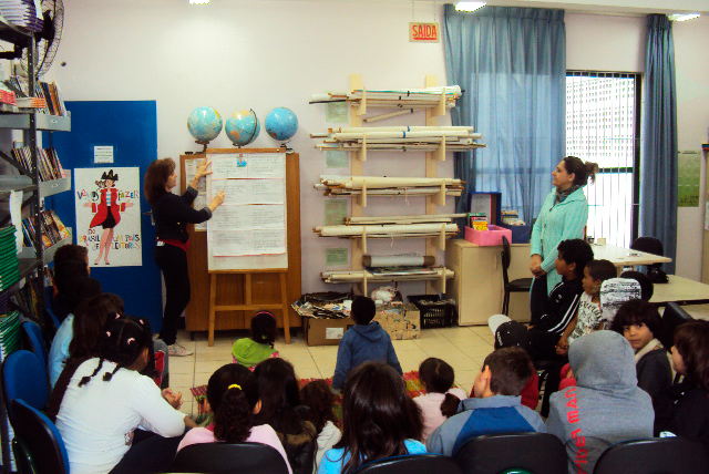 Em sala de aula, crianças sentadas observam apresentação de educadora em painel. De pé, outra educadora também assiste à apresentação. Fim da descrição.