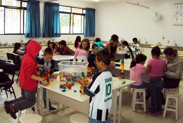 Em sala de aula, crianças realizam diversas atividades acompanhados de educadoras. Na mesa mais próxima, três meninos utilizam blocos coloridos para montar figuras. Fim da descrição.