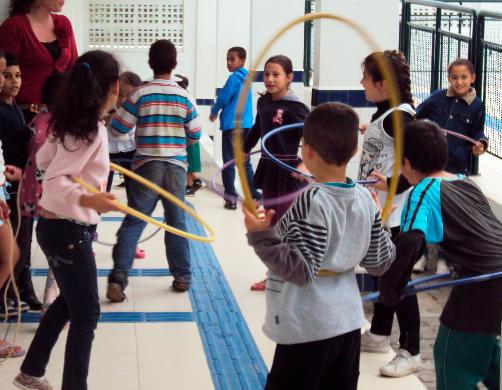 Em corredor da escola, diversas crianças brincam juntas. Algumas delas utilizam bambolês coloridos. O chão da escola possui piso tátil. Fim da descrição.