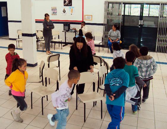 """Educadora auxilia crianças na brincadeira """"dança da cadeira"""". Nove meninos e meninas participam da atividade, andando em volta de cadeiras postas em círculo. Outras educadoras observam ao fundo. Fim da descrição."""