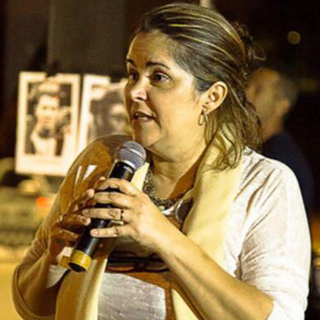 Eugênia Gonzaga segura microfone com as duas mãos. Ela é uma mulher branca na faixa dos 40 anos. Tem os cabelos castanhos e mechas loiras. Fim da descrição.