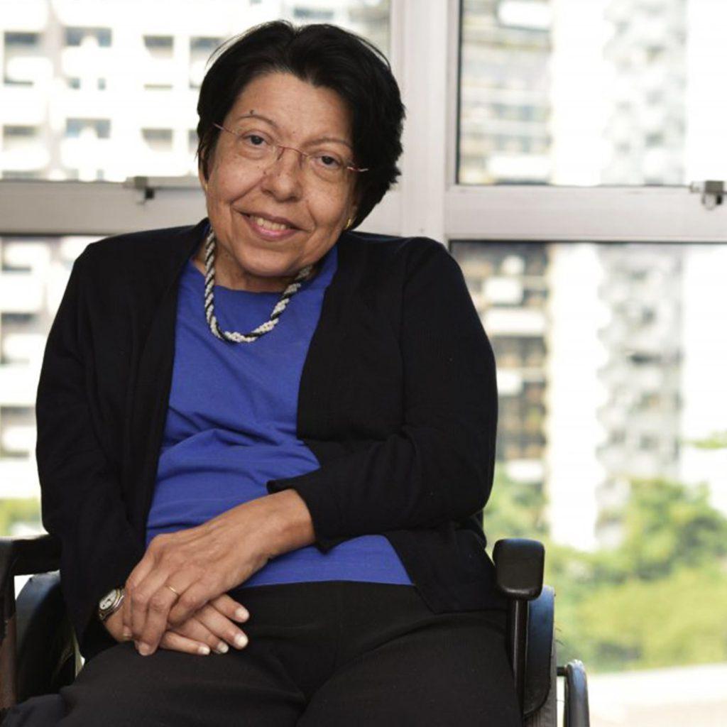 Izabel Maior, sentada em cadeira de rodas e com uma mão apoiada sobre a outra, posa para foto sorridente. Ela é uma mulher negra na faixa dos 50 anos. Uusa uma blusa preta, uma camisa azul e um colar em branco e preto. Fim da descrição.
