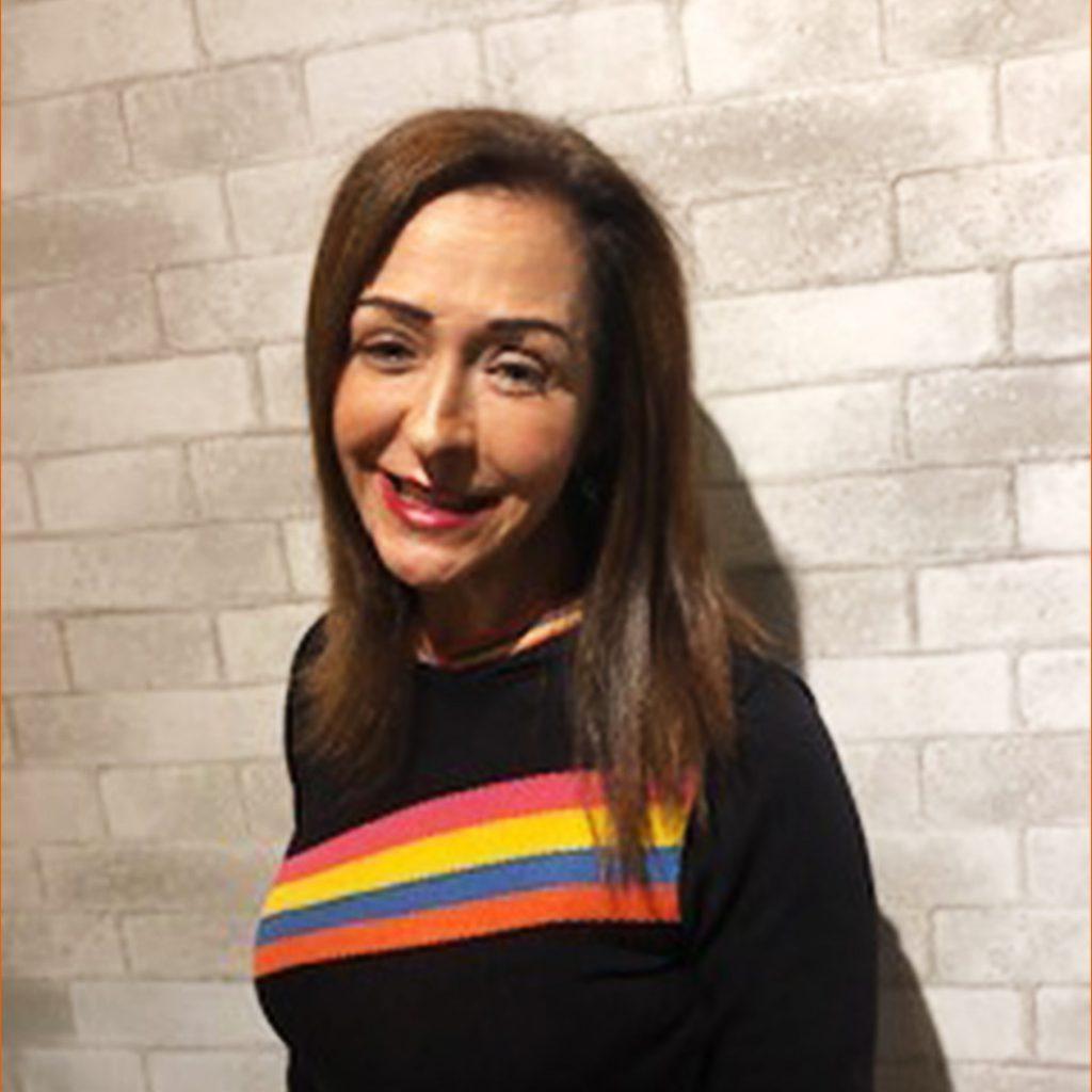 Martinha Clarete Dutra sorri em frente à parede de tijolos. Ela é uma mulher branca e veste uma camisa preta com listras na altura do peito. em rosa, amarelo, azul e laranja. Fim da descrição.