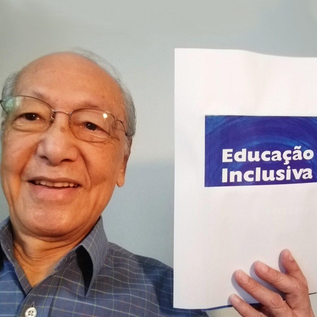 """Romeu Kazumi Sassaki sorri enquanto segura com a mão esquerda uma folha de sulfite com as palavras """"educação inclusiva"""". Ele usa óculos e tem cabelos brancos. Fim da descrição."""