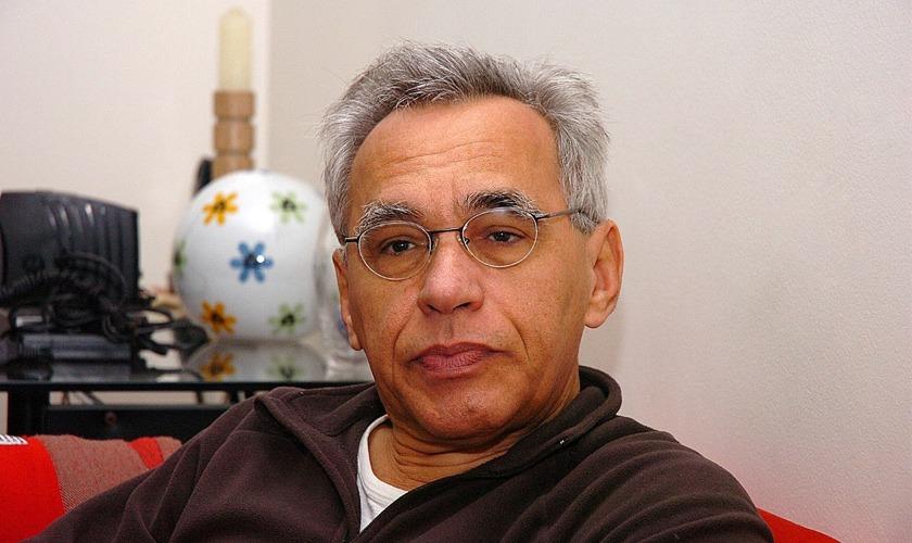 Lino está sentado em sofá. Ele tem cabelos grisalhos, está na faixa dos 60 anos e usa óculos com lentes arredondadas. Fim da descrição.