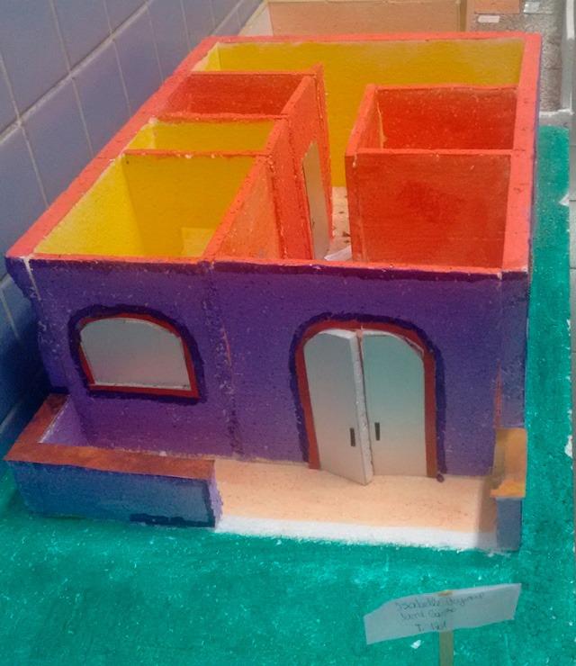 Maquete escolar de uma casa de três cômodos. As paredes externas estão cor roxa, enquanto as internas recebem o amarelo e o laranja. Fim da descrição.