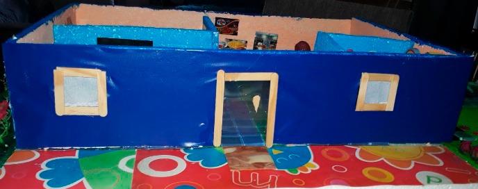 Parte externa e plana de maquete escolar de uma casa. As paredes estão pintadas na cor azul. Fim da descrição.