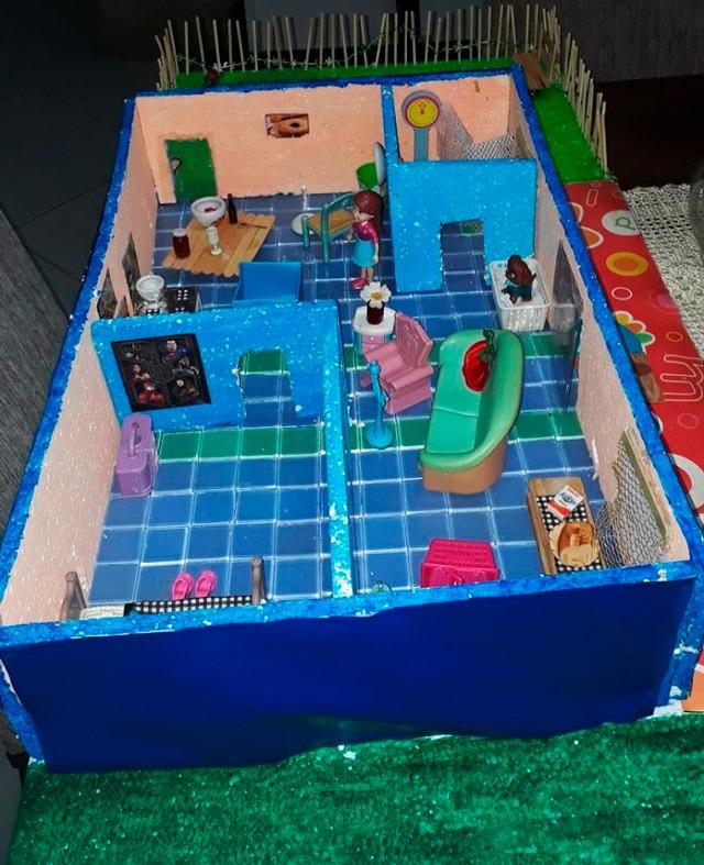 Visão aérea de maquete escolar de uma casa de três cômodos: sala, cozinha e quarto. Fim da descrição.