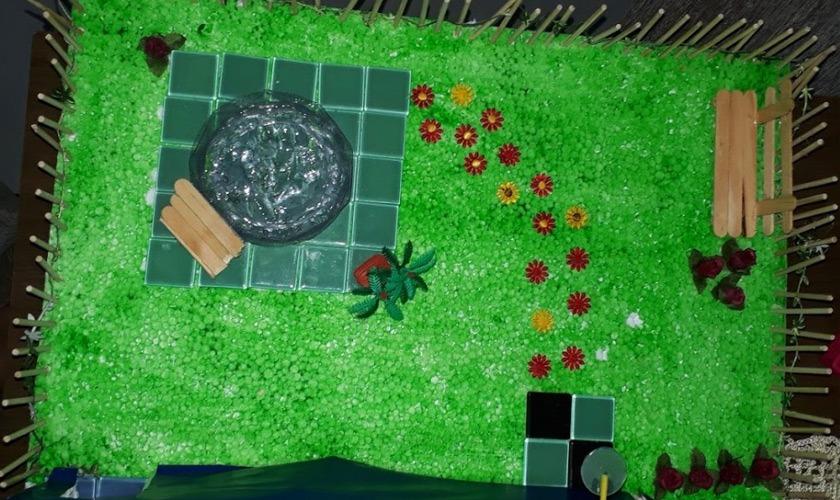 Imagem aérea de um jardim de uma maquete escolar. Há uma piscina circular feita de plástico, flores e uma esteira de madeira. Fim da descrição.