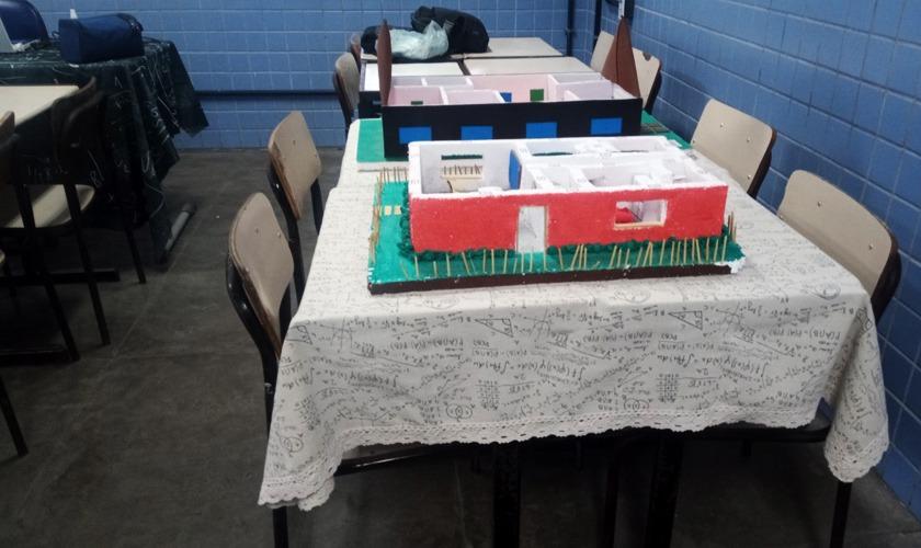 Em sala de professores, maquetes estudantis de casa populares estão expostas. Fim da descrição.