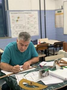 Em sala de aula, professor Luiz Felipe Lins desenha em folha de sulfite utilizando réguas. Ele está sentado em carteira escolar.
