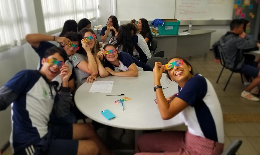 Em sala de aula, grupo com quatro alunos sorri para a câmera. Cada um segura um par de óculos de difração sobre os olhos. Fim da descrição.