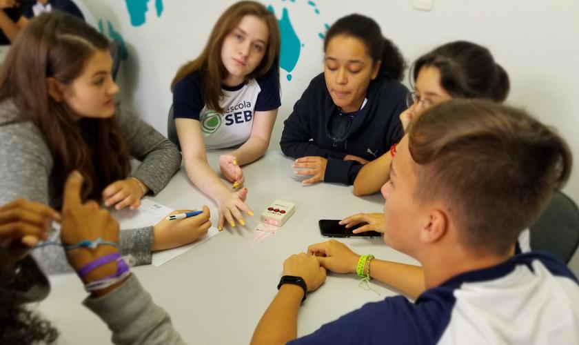 Estudantes sentados em volta de mesa redonda conversam entre si e observam laser vermelho ao centro. Um deles faz anotações em papel. Fim da descrição.