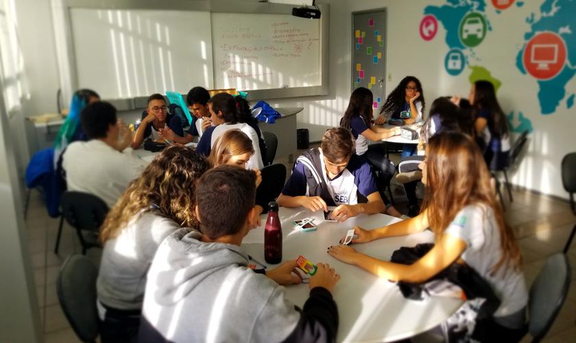 Em sala de aula, estudantes divididos em grupos estão sentados em volta de mesas redondas. Na mesa mais próxima, o grupo realiza atividade com óculos de difração. Fim da descrição.