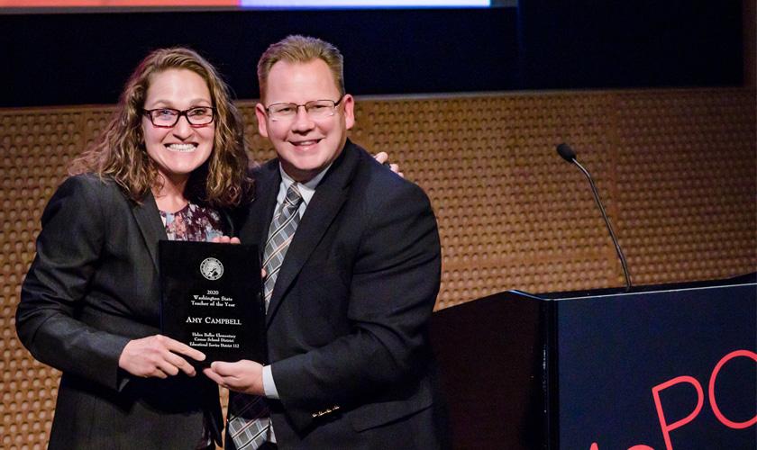 Em palco, educadora Amy Campbell, abraçada a apresentador, recebe placa preta com nomeação de educadora do ano do estado de Washington. Ambos sorriem para a câmera. Fim da descrição.
