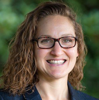 Amy Campell, mulher branca, com cabelo ondulado castanho claro, sorri para a câmera. Ela usa óculos com armação retangular escura e sorri para a câmera. Fim da descrição.
