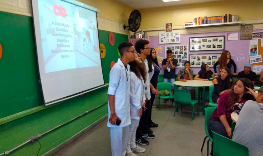 Em sala de aula, quatro estudantes vestindo jalecos brancos se apresentam para o restante da classe. Ao fundo, apresentação de tela sobre a lousa. Fim da descrição.