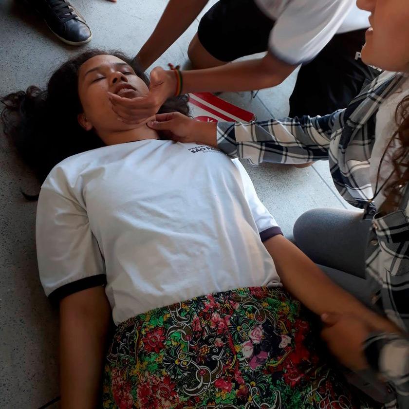 Em performance, estudante está deitada sobre o chão, com os olhos fechados, enquanto seus colegas estão sentados à sua volta e chegam seus sinais vitais. Fim da descrição.