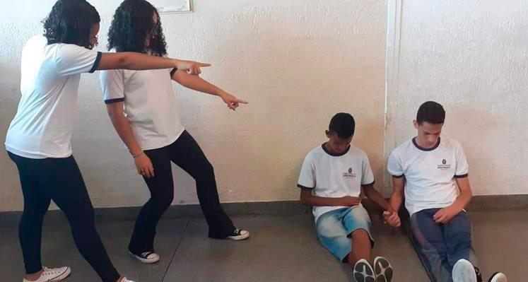 Em performance, duas estudantes fazem chacota de dois meninos que estão sentados no chão, cabisbaixos. Fim da descrição.