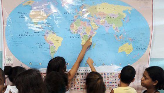Em sala de aula estudantes se aglomeram em frente a mapa mundo fixado em parede. Alguns deles colocam o dedo indicador sobre alguns países da África. Fim da descrição.