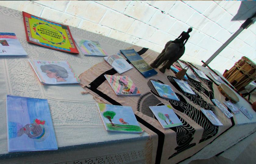 Sobre mesa desenhos produzidos por estudantes de imagens representativas da África. Há também livros e instrumentos musicais. Fim da descrição.