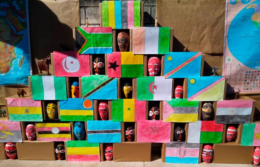 Em exposição, bandeiras de países africanos em composição com máscaras africanas. Fim da descrição.