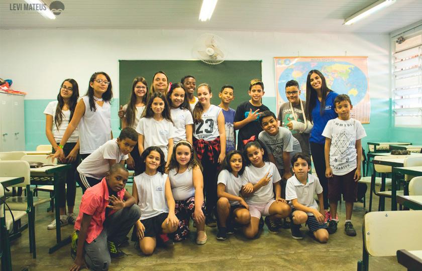 Em sala de aula, estudantes uniformizados com camisas brancas posam para foto ao lado de educadora. Alguns estão de pé, enquanto outros fazem fileira à frente agachados. Fim da descrição.