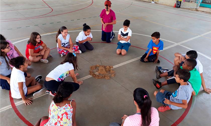 Estudantes sentam em círculo sobre faixa central da quadra esportiva e observam material construído com terra. Fim da descrição.