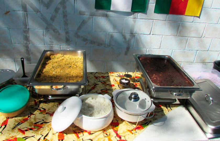 Sobre mesa com pano de prato com imagens de mulheres vestidas com roupas típicas da África, há pratos com farofa, arroz e feijoada. Fim da descrição.